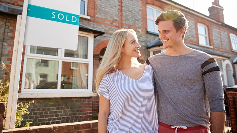 Male and female couple stadning outside their new home with a sold sign